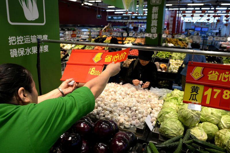 FILE PHOTO: Staff member inserts a price tag for vegetable at a Walmart in Beijing