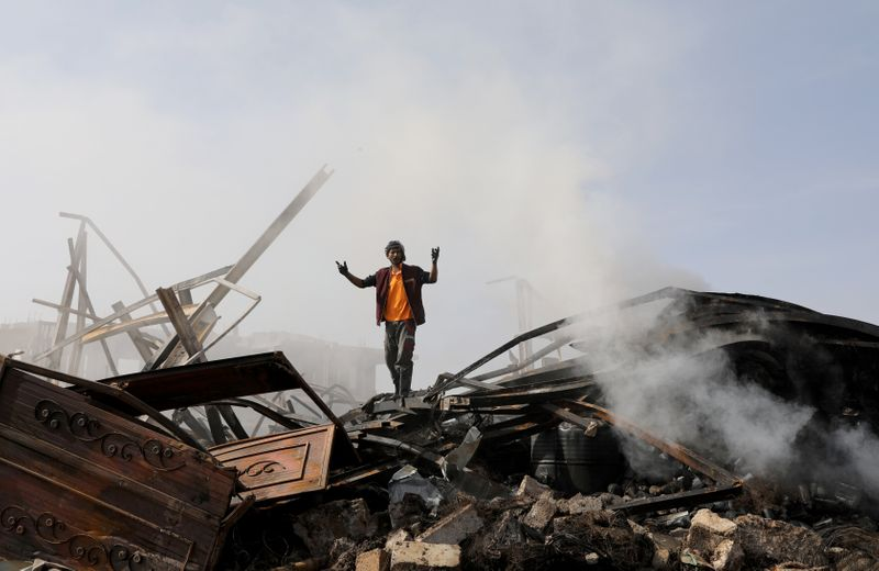 A worker reacts as he stands on the wreckage of a vehicle oil and tires store hit by Saudi-led air strikes in Sanaa