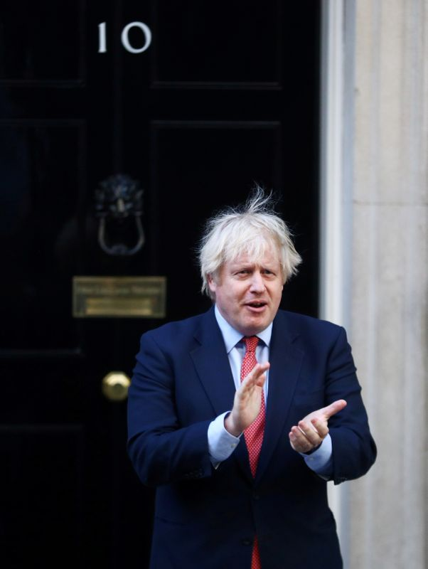 FILE PHOTO: British Prime Minister Boris Johnson applauds the NHS outside 10 Downing Street in May