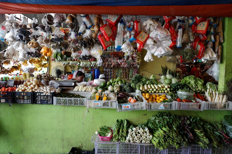 A woman waits for customers inside a food market in Paranaque, Metro Manila