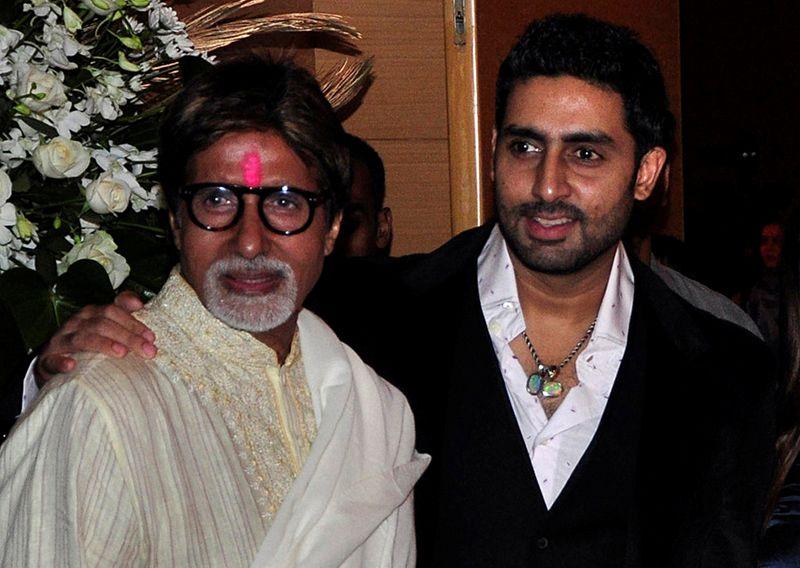 FILE PHOTO: Bollywood actors Amitabh and Abhishek Bachchan pose in Mumbai