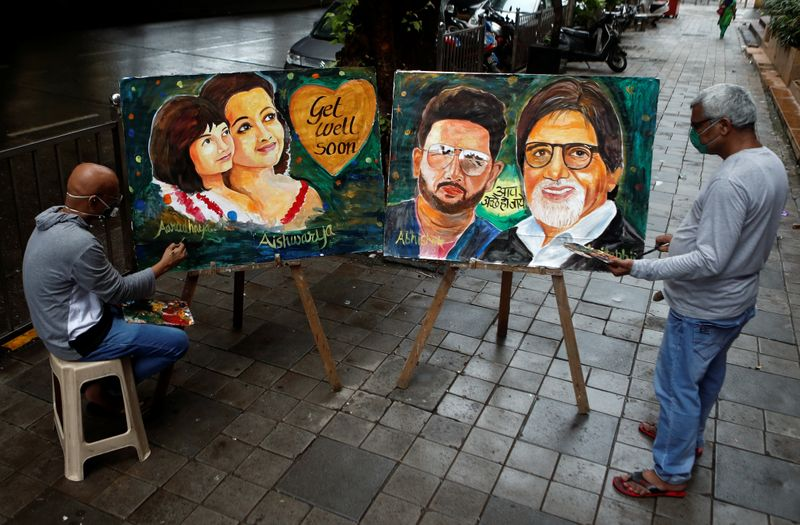 Artists create paintings depicting Bollywood actor Amitabh Bachchan, his son Abhishek Bachchan, his daughter-in-law Aishwarya Rai Bachchan and his granddaughter Aaradhya, after they tested positive for the coronavirus disease (COVID-19), in Mumbai
