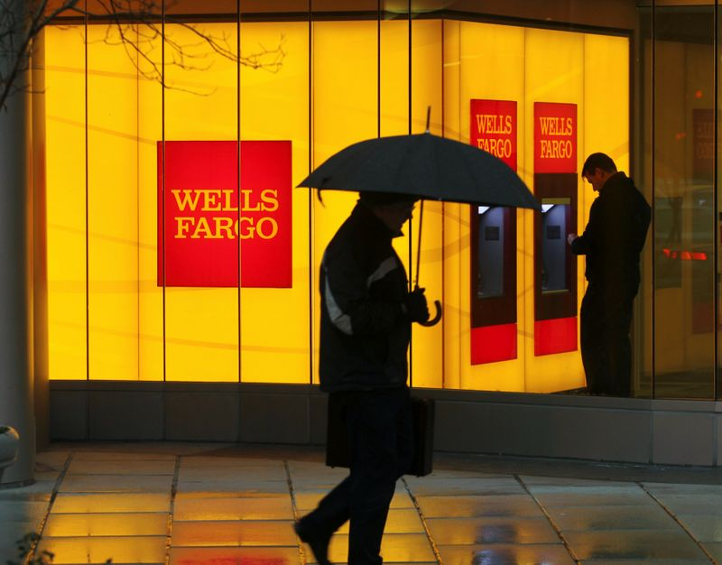 FILE PHOTO: FILE PHOTO: A man walks past a Wells Fargo Bank branch on a rainy morning in Washington