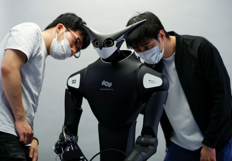Staff members of Telexistence check the copmany's shelf-stacking avatar robot, designed to resemble a kangaroo and developed to work in a convenience store, during a photo opportunity ahead of its unveiling in Tokyo, Japan