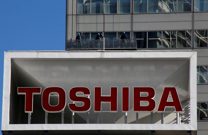 FILE PHOTO: Logo of Toshiba Corp is seen as Window cleaners work on the company's headquarters in Tokyo