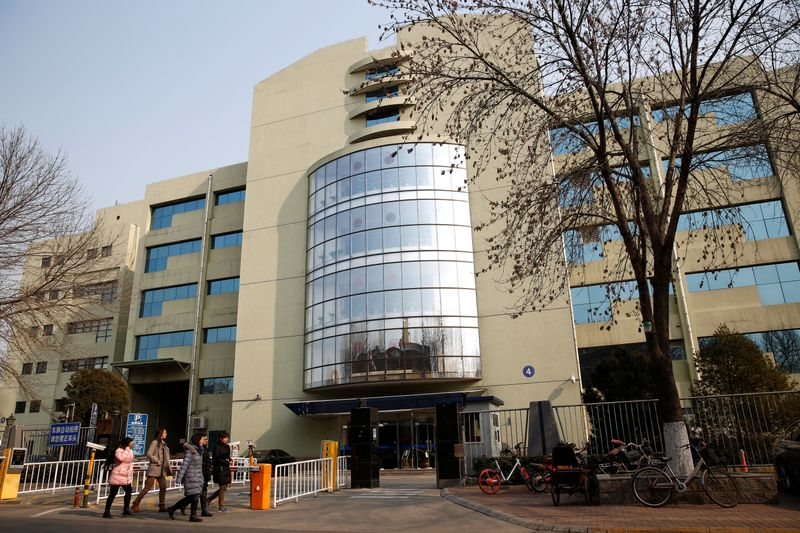 People walk past the building with the listed address of Tomorrow Holdings' Beijing office