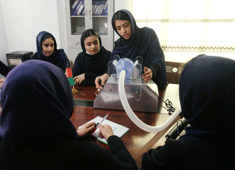 Members of an Afghan all-female robotics team work on an open-source and low-cost ventilator in Herat