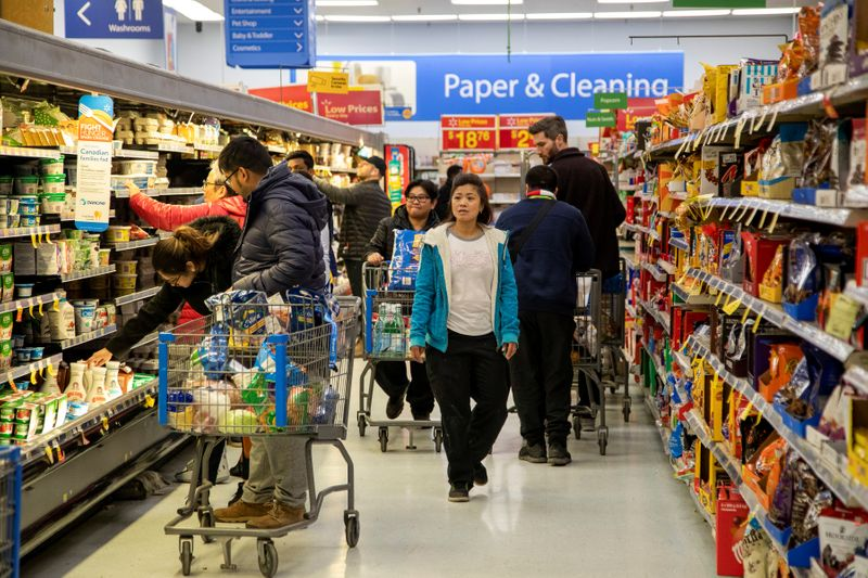 People gather supplies at a grocery store amid coronavirus fears spreading in Toronto,