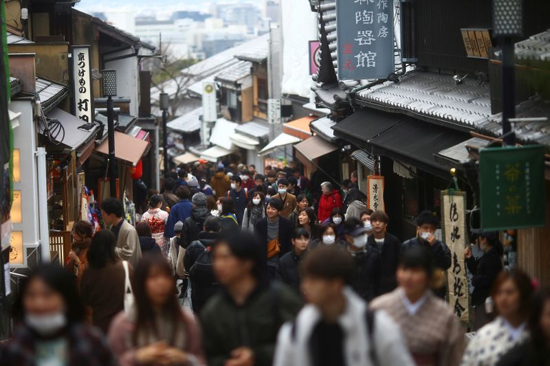 FILE PHOTO: People, wearing protective masks following an outbreak of the coronavirus disease (COVID-19), walk on a street of Gion district in Kyoto