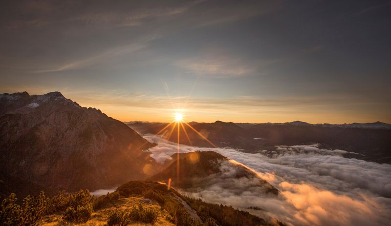 FILE PHOTO: The sun rises over mountain summits in the Austrian village of Absam