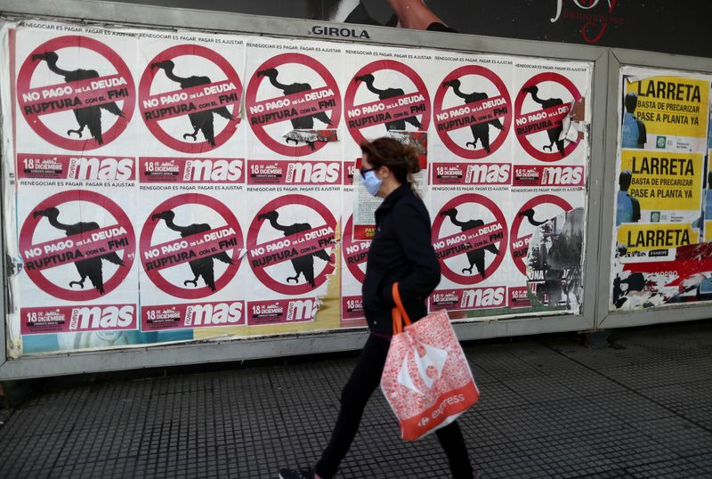 FILE PHOTO: A pedestrian wearing a protective face mask walks past posters on the street that read