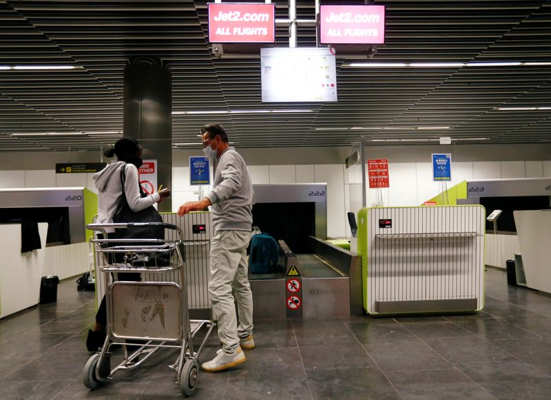 FILE PHOTO: British tourists returning to UK, check in their luggage, as Britain imposed a two-week quarantine on all travellers arriving from Spain