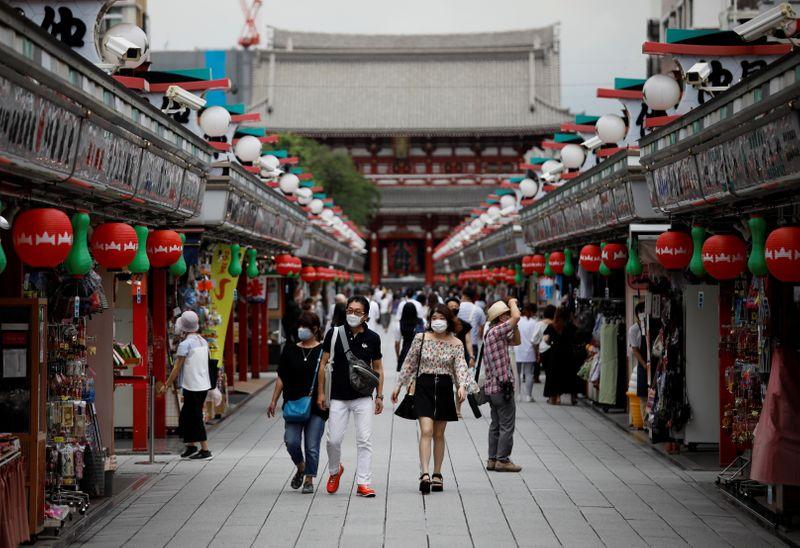 Visitors wearing protective face masks walk at Asakusa district amid the coronavirus disease (COVID-19) outbreak in Tokyo