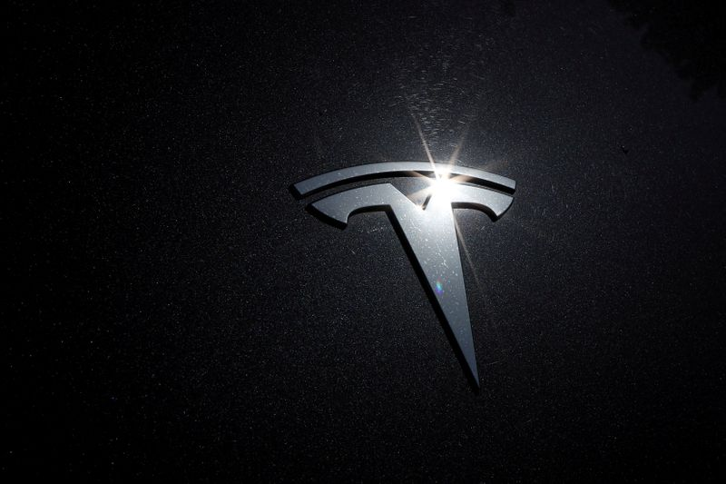 FILE PHOTO: The Tesla logo is seen on a car in Los Angeles