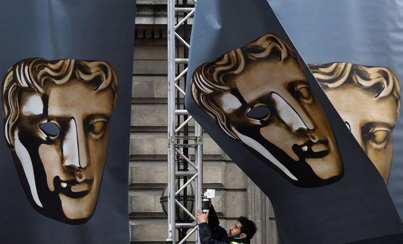 FILE PHOTO: An event worker attaches set parts during preparations for the BAFTA awards ceremony in London