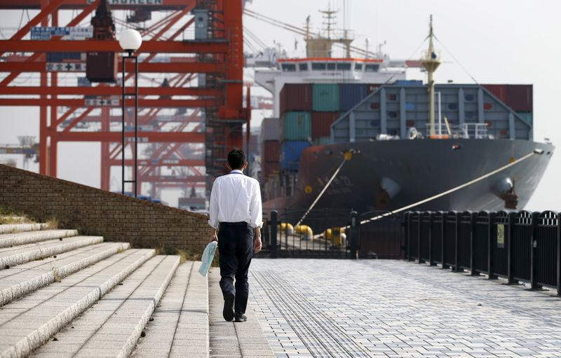 A man walks near a container ship at a port in Tokyo