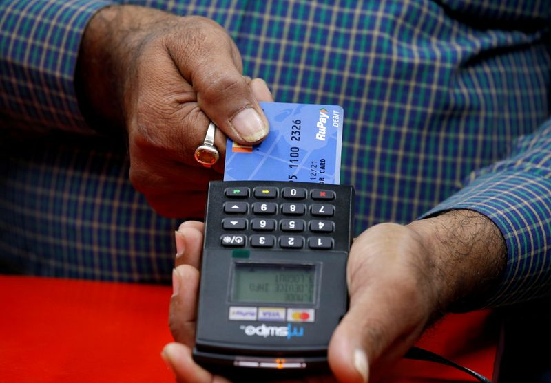 FILE PHOTO: A shopkeeper swipes a customer's debit card with the logo of RuPay at an electronics goods store in Kolkata