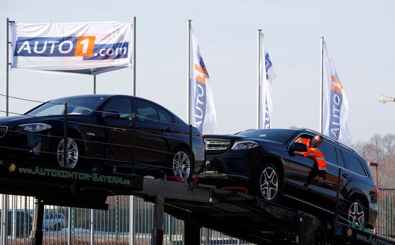A worker loads a second hand car on a car transporter truck at the Auto1.com company grounds in Zoerbig