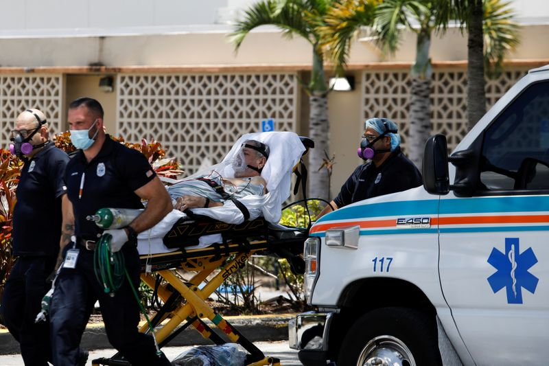 FILE PHOTO: Emergency Medical Technicians (EMT) leave with a patient at Hialeah Hospital where the coronavirus disease (COVID-19) patients are treated