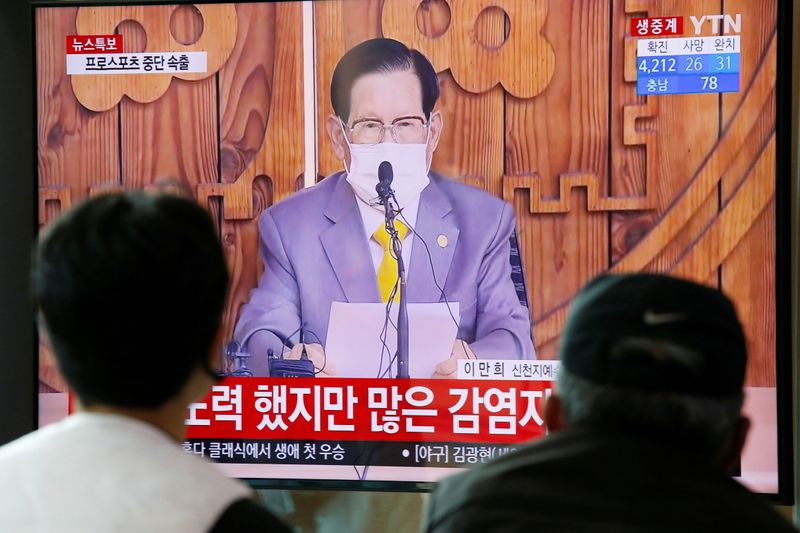 People watch a TV broadcasting  a news report on a news conference held by Lee Man-hee, founder of the Shincheonji Church of Jesus the Temple of the Tabernacle of the Testimony, in Seoul