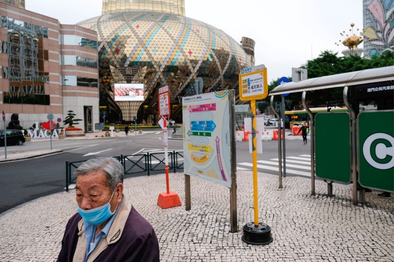 FILE PHOTO: A man wears a mask as he walks in front of the closed Grand Lisboa casino in Macau