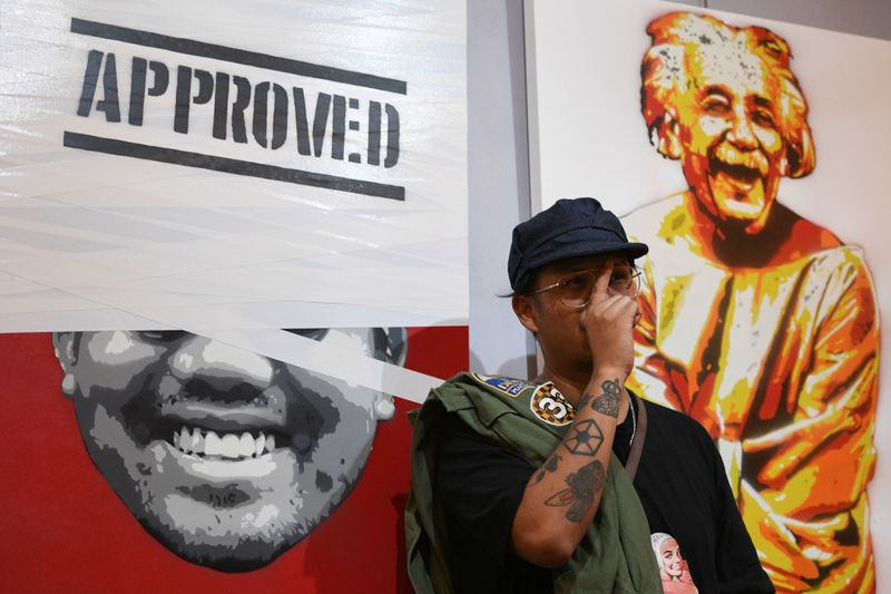 Headache Stencil, a graffiti artist poses in front of his works during his exhibition at The Foreign Correspondents' Club of Thailand (FCCT) in Bangkok