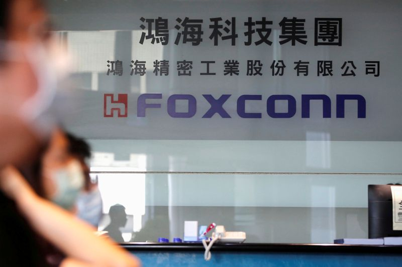FILE PHOTO: People wear masks to protect themselves from coronavirus disease (COVID-19), while listening to the annual general meeting at the lobby of Foxconn's office in Taipei