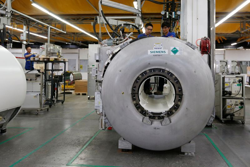 Staff work on magnetic resonance imaging machines at a production line of Siemens Healthineers in Shenzhen