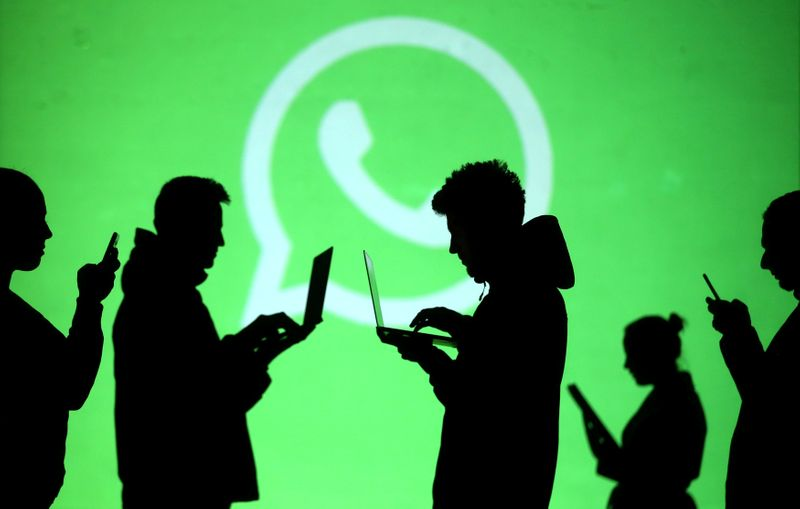 FILE PHOTO: Silhouettes of laptop and mobile device users are seen next to a screen projection of Whatsapp logo in this picture illustration