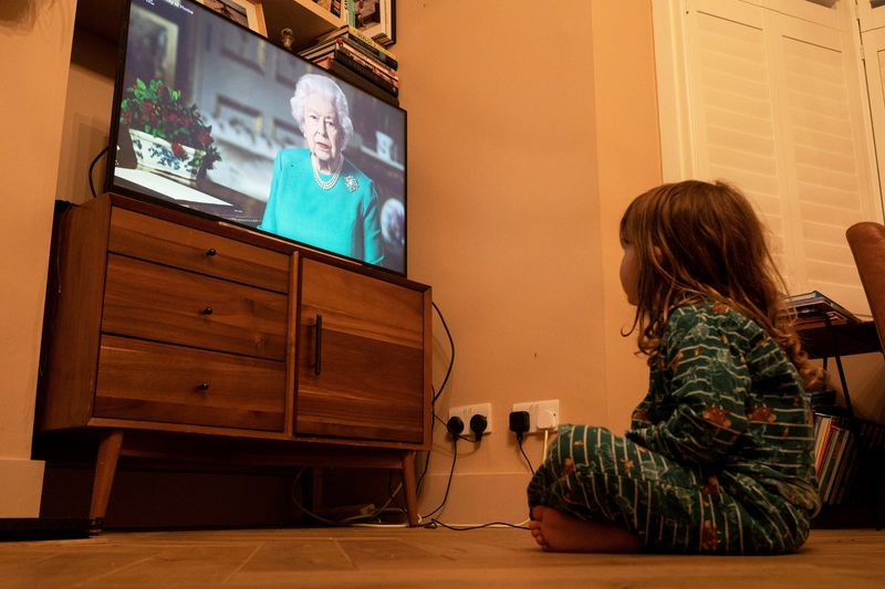 FILE PHOTO: Isaac (4) watches Queen Elizabeth II during a televised address to the nation