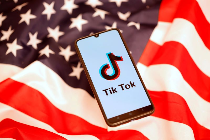 FILE PHOTO: TikTok logo is displayed on the smartphone while standing on the U.S. flag in this illustration