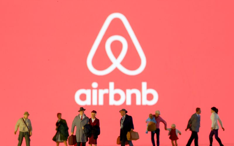 Small toy figures are seen in front of diplayed Airbnb logo