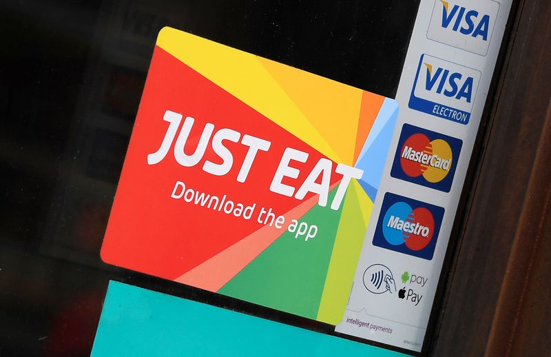 Signage for Just Eat is seen on the window of a restaurant in London