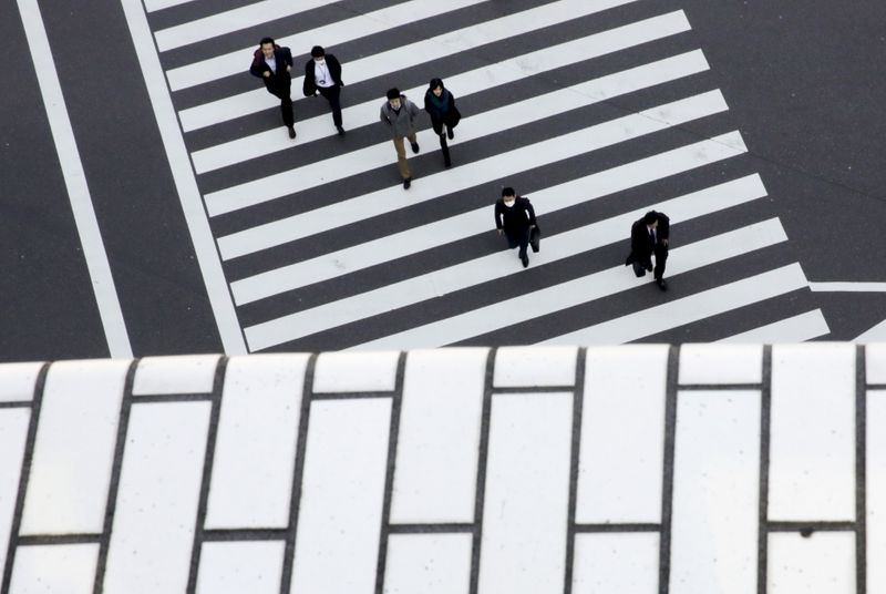 FILE PHOTO: People cross a street in a business district in Tokyo