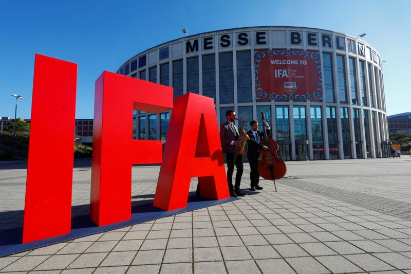 Musicians play on their instruments next to an IFA sign, in Berlin