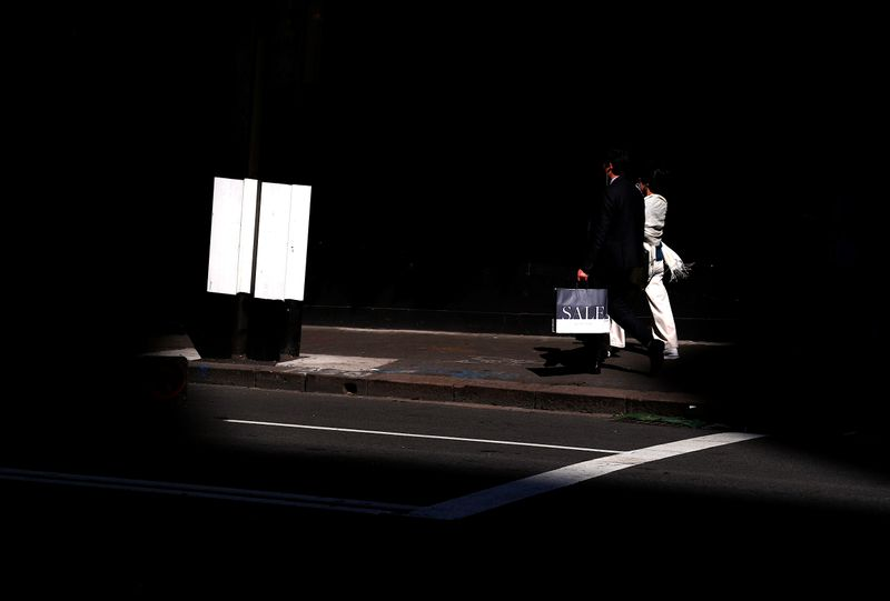 A shopper carries a bag displaying the word 'Sale' as he walks along a footpath outside a retail store in central Sydney