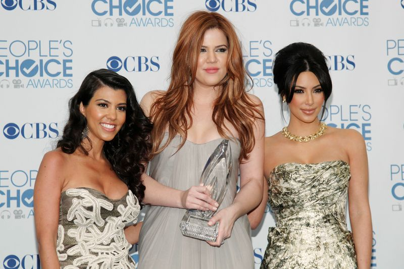 FILE PHOTO: Reality TV sisters Kourtney, Khloe and Kim Kardashian pose with their favorite guilty pleasure award at the 2011 People's Choice Awards in Los Angeles