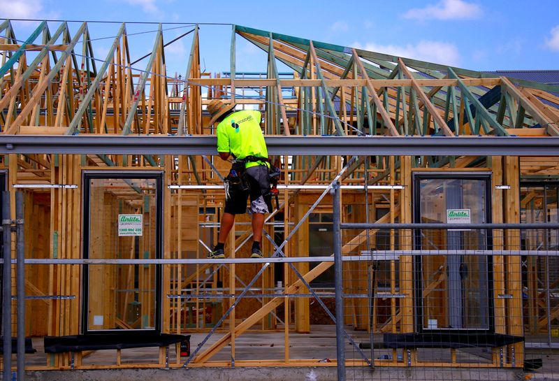 A tradesman works on the roof of a house under construction at a housing development located in the western Sydney suburb of Oran Park