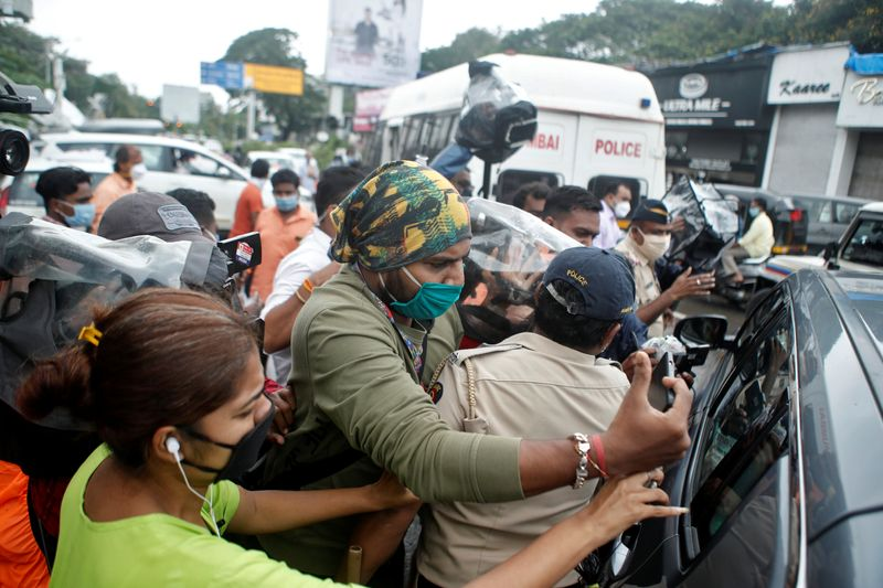A policeman holds off media personnel as they surround a car carrying Bollywood actor Rhea Chakraborty as she heads to CBI office for questioning, in Mumbai