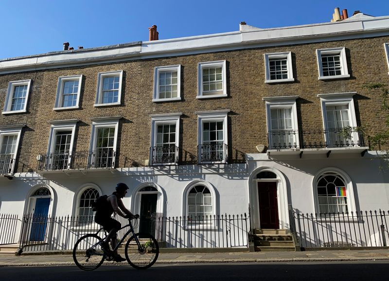 FILE PHOTO: A cyclist rides past houses on a street in Islington, London