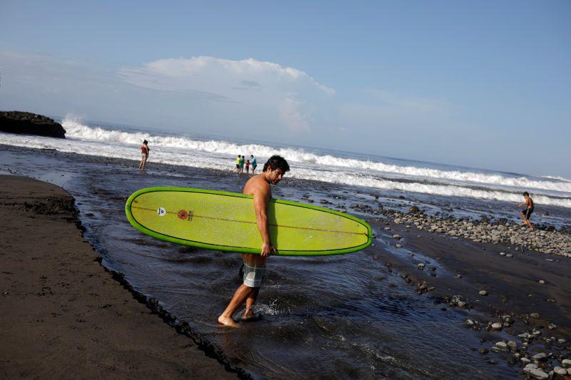 FILE PHOTO: Surfer crosses a stream at El Tunco beach in Tamanique