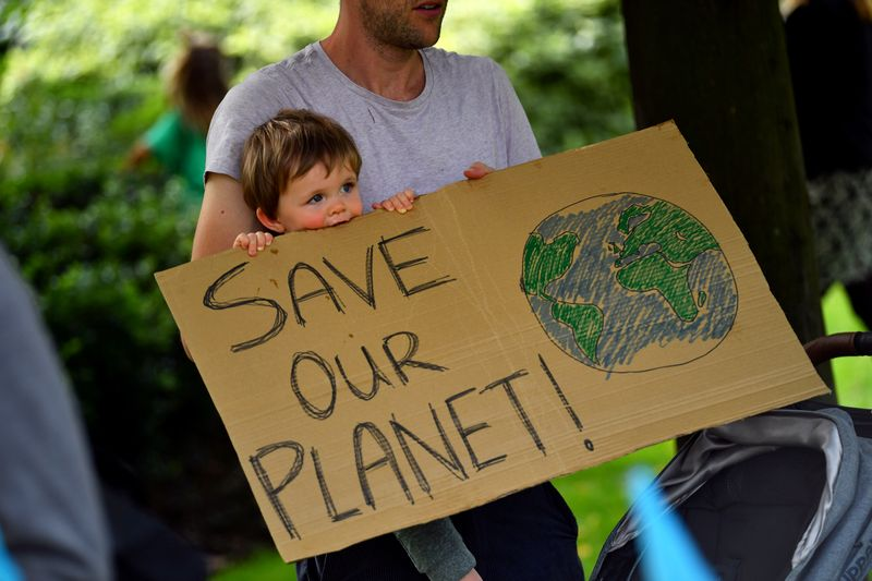 FILE PHOTO: A father and his child are holding a sign as climate activists protest in London