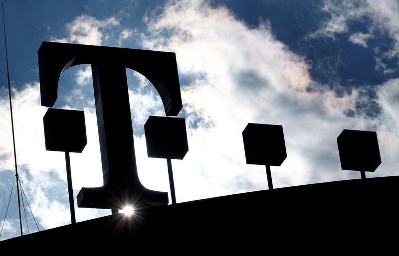 FILE PHOTO: The logo of Deutsche Telekom AG is silhouetted against the sun and clouds atop of the headquarters of German telecommunications giant in Bonn