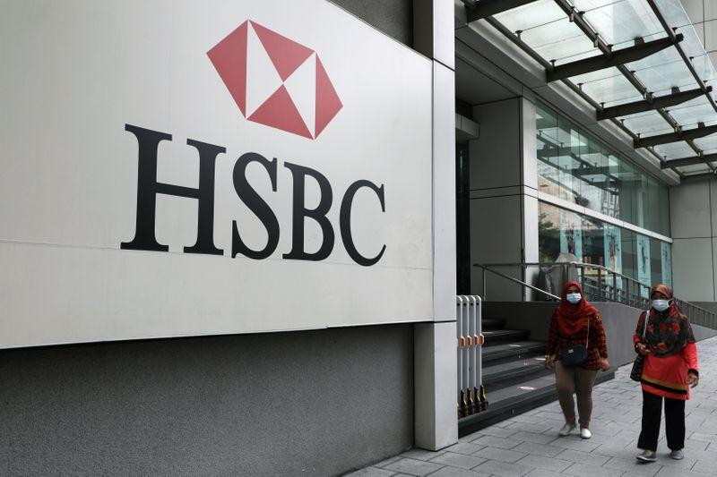 Women wearing protective masks walk past HSBC headquarters, amid the coronavirus disease (COVID-19) outbreak in Kuala Lumpur