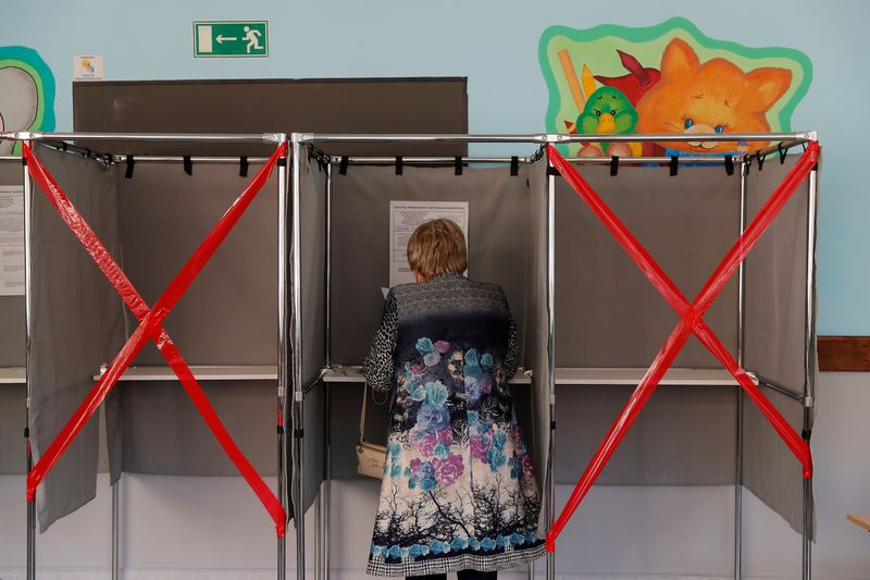 Woman checks her ballot in a voting booth during local elections in the Siberian city of Tomsk