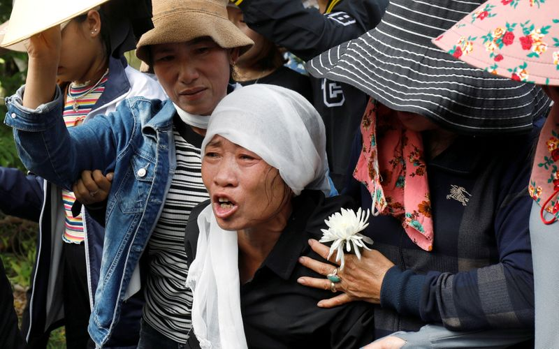 FILE PHOTO: Tran Thi Hien cries while following an ambulance carrying her daughter's coffin during the funeral ceremony at her village in Nghe An province