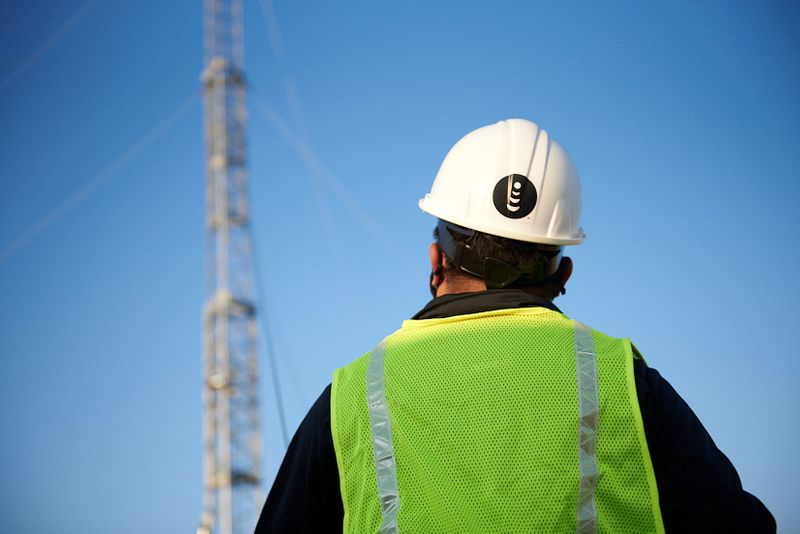 A worker stands in front of a mobile tower in Denver