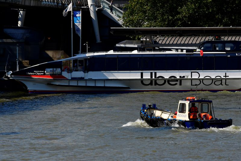 Uber signage is seen on the side of a river taxi on the river Thames, in London
