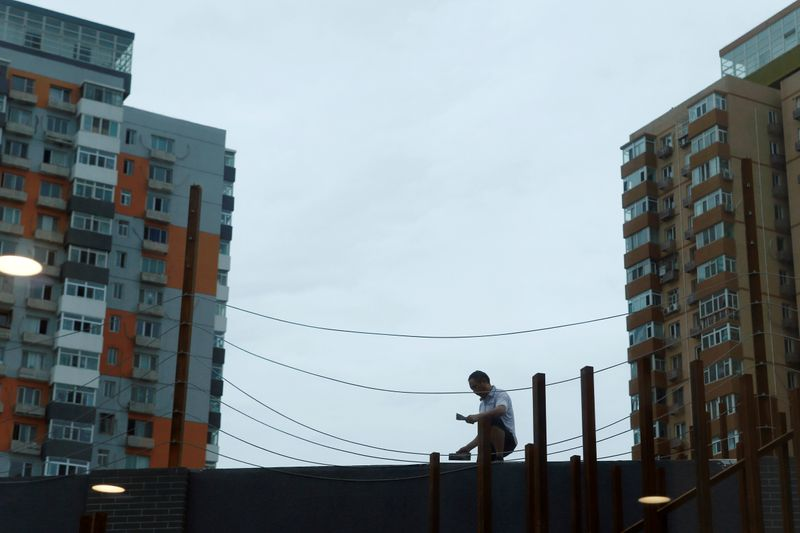 Man works on renovating an office building near residential buildings in Beijing