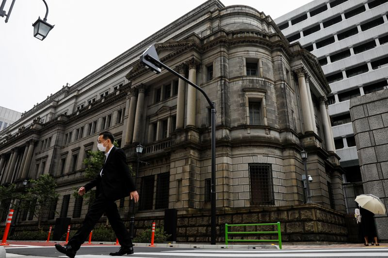 A man wearing a protective mask walks past the headquarters of Bank of Japan amid the coronavirus disease (COVID-19) outbreak in Tokyo